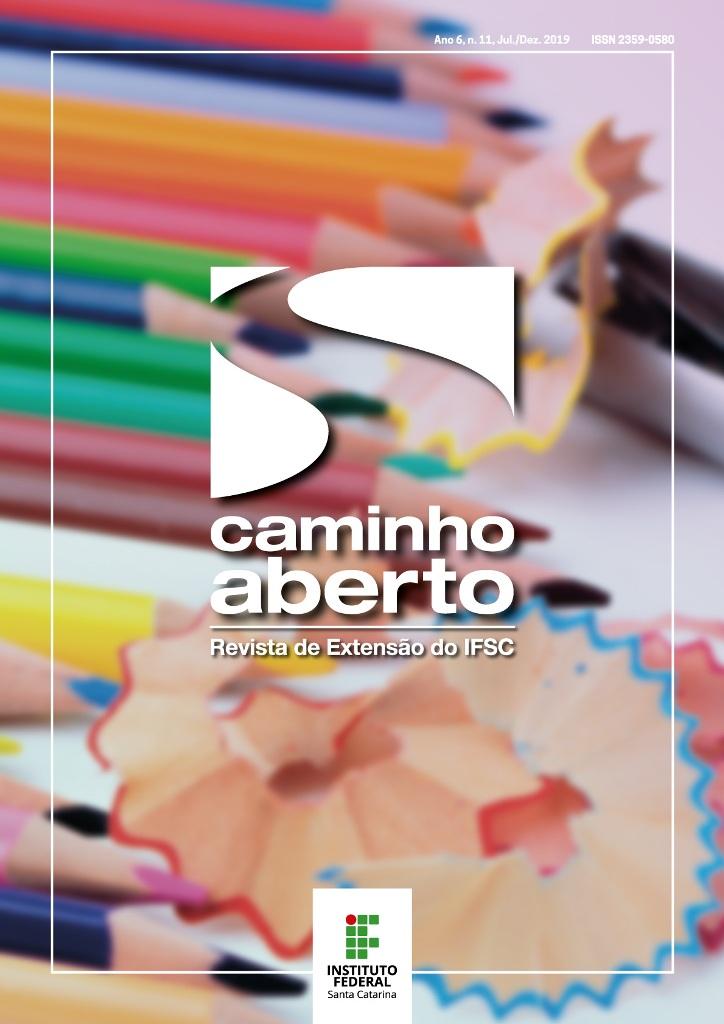 Capa da revista contém imagem com vários lápis de cores diferentes lado a lado sobre uma mesa. Há resto de ponta de lápis apontado entre alguns lápis.